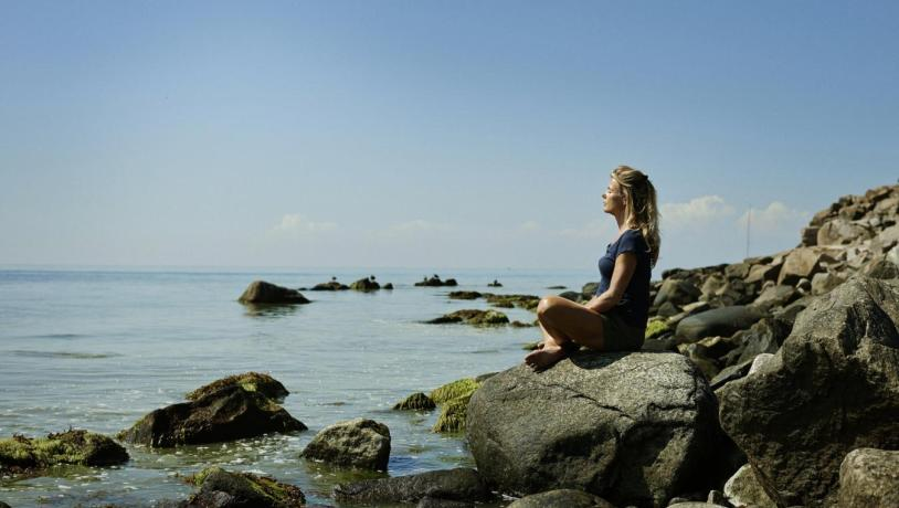 Lady sat relaxing on a beach in Bornholm