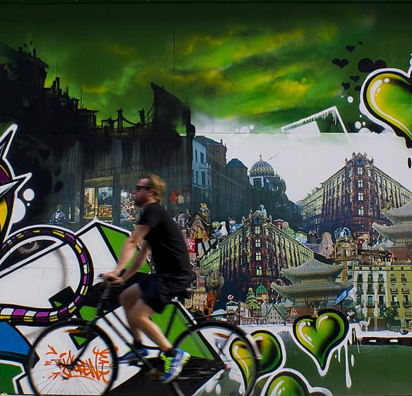 A cyclist rides past a graffiti wall covered with green hearts
