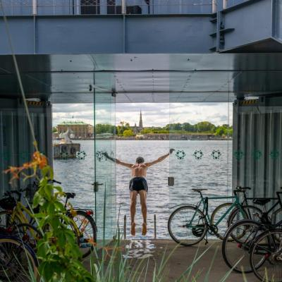 A man swims from the Urban Rigger student housing block designed by Bjarke Ingels Group in Copenhagen, Denmark