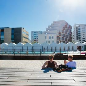 People enjoying the sun beside the harbour bath in Odense, Denmark